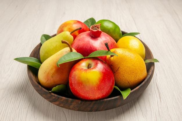 흰색 책상 과일 익은 나무에 있는 접시 안에 있는 신선한 과일 사과 배 및 기타 과일은 많은 신선한 과일을 부드럽게 합니다.