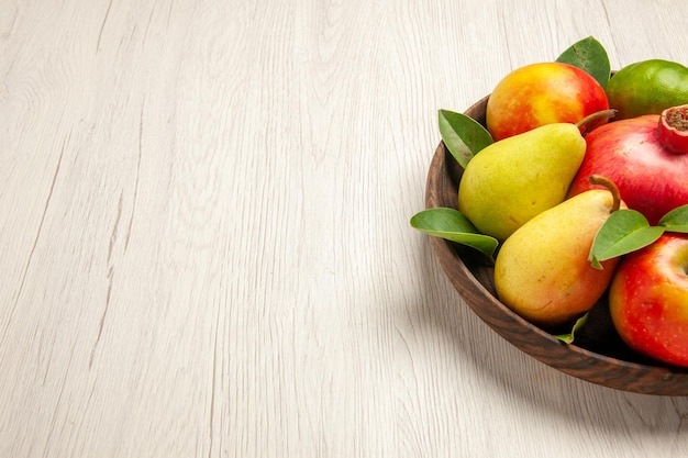 Front view fresh fruits apples pears and other fruits inside plate on the white desk fruits ripe tree mellow many fresh