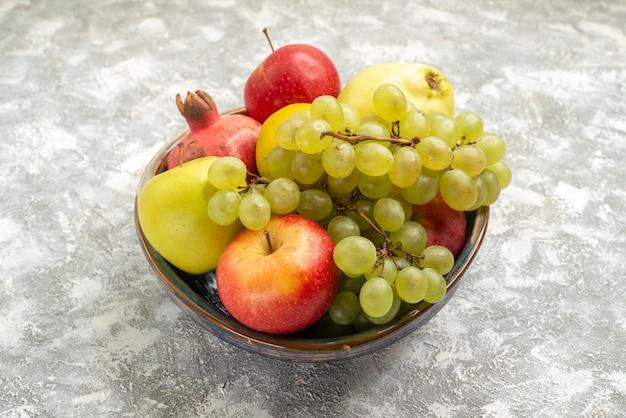 Vista frontale frutta fresca composizione mele uva e altri frutti su sfondo bianco frutta fresca e pastosa colore maturo vitamina