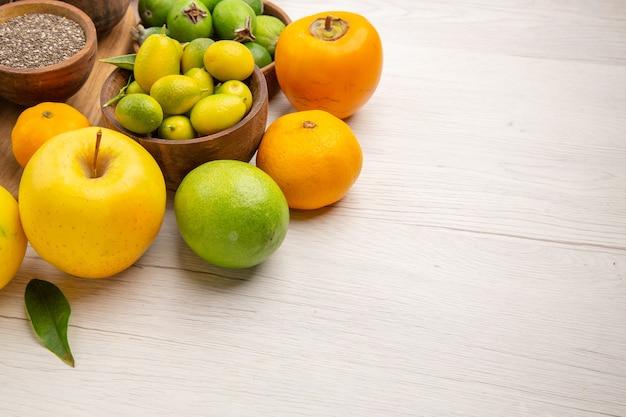 Вид спереди свежие фрукты композиция разные фрукты на белом фоне здоровье цвет цитрусовых деревьев спелые вкусные диета экзотические