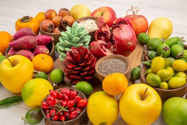 Вид спереди свежие фрукты композиция разные фрукты на белом фоне вкусное здоровье цитрусовое дерево цвет ягодная диета экзотика