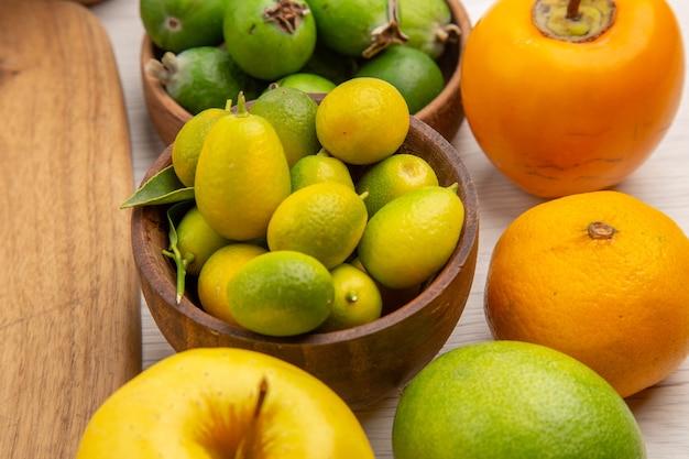 Вид спереди композиция из свежих фруктов на белом фоне ягоды цитрусовые здоровье дерево цвет фото спелые фрукты вкусные
