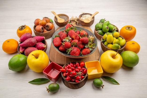 Вид спереди композиция из свежих фруктов на белом фоне фото цветная ягода цитрусовое дерево здоровья спелые фрукты вкусно