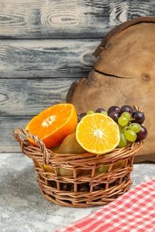 正面図新鮮な果物のブドウと白い背景の上のバスケット内のスライスされたオレンジ果物熟したまろやかなビタミン新鮮