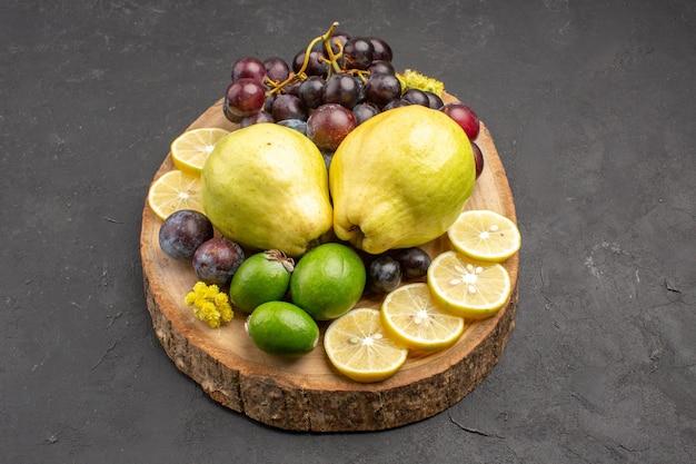 Vista frontale frutta fresca uva fette di limone prugne e mele cotogne sullo sfondo scuro frutta fresca pianta matura albero