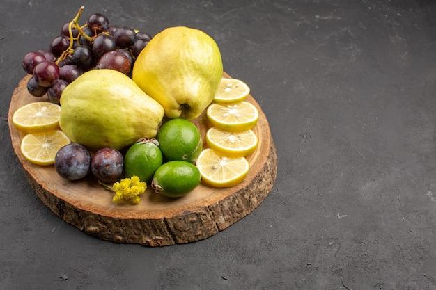 Vista frontale frutta fresca uva fette di limone prugne e mele cotogne su sfondo scuro frutti pianta fresca e matura
