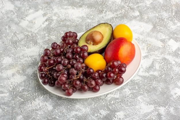 Vista frontale frutta fresca uva pesca e avocado all'interno della piastra sulla superficie bianca