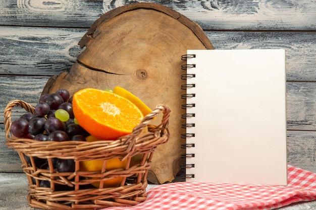 Vista frontale frutta fresca uva e arance a fette all'interno del cestello su sfondo grigio frutta matura vitamina dolce fresca