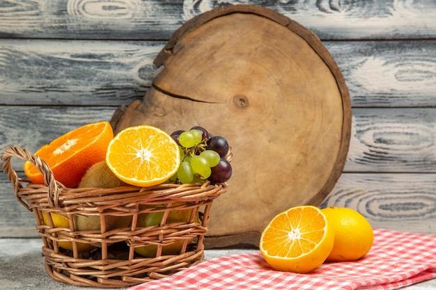 Vista frontale frutta fresca uva e arance a fette all'interno del cestello su sfondo bianco frutta matura vitamina dolce fresca