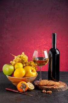 Вид спереди свежие фрукты в миске яблоко айва виноград хурма бутылка вина бокал вина печенье на деревянной доске на красном столе