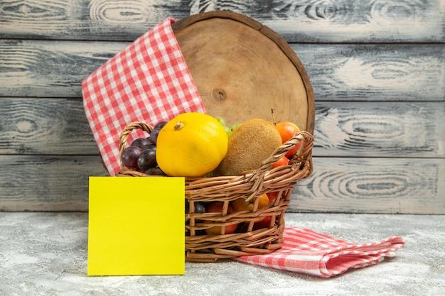 Vista frontale frutta fresca all'interno del cesto sul colore grigio del quaderno degli agrumi della frutta