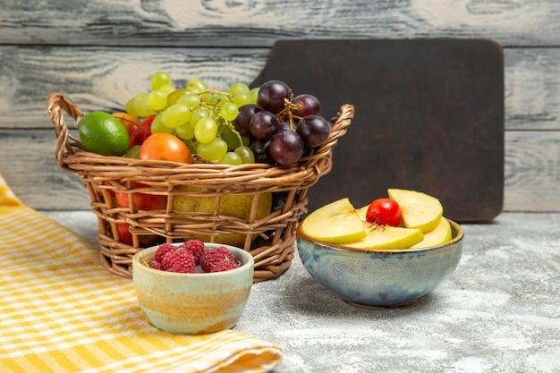 Vista frontale frutta fresca all'interno del cesto su sfondo grigio frutta matura matura