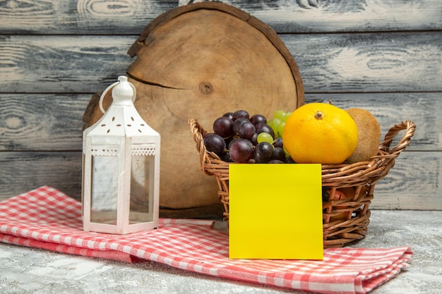 灰色の背景のフルーツ柑橘類のコピーブックの色のバスケット内の新鮮な果物の正面図