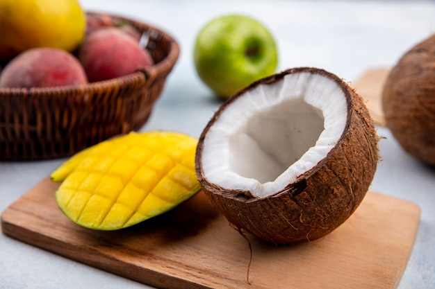 Front view of fresh fruits like sliced mango and half coconut on a wooden kitchen board with apples and peaches on a bucket on white surface