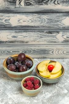 正面図新鮮な果物プラムラズベリーと灰色の背景にリンゴ熟した果物まろやかな新鮮