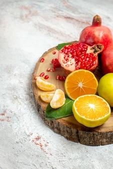Вид спереди свежие фрукты гранаты и мандарины на белом пространстве