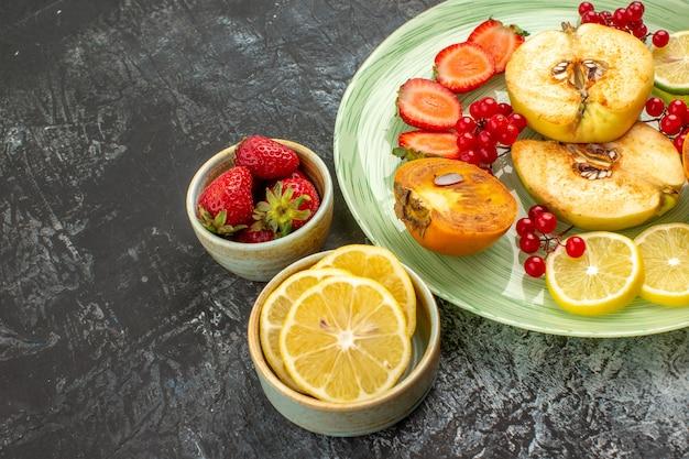 Vista frontale frutta fresca mele cotogne limoni e altri frutti sul tavolo luminoso