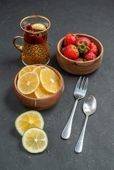 Вид спереди свежие фрукты клубники и лимоны на сером фоне