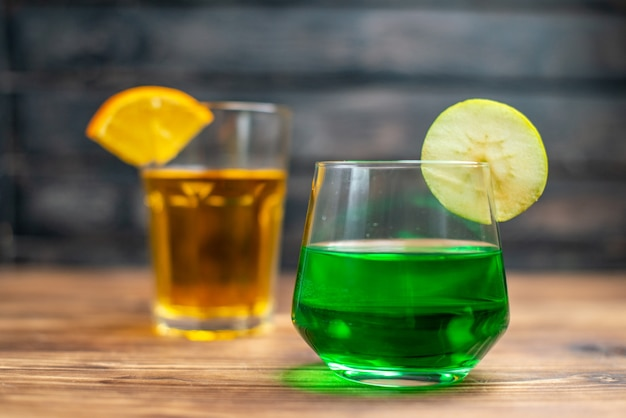 Вид спереди свежие фруктовые соки апельсиновые и яблочные напитки в очках на коричневом деревянном столе