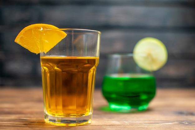 Front view fresh fruity juice orange and apple drinks inside glasses on brown wooden desk drink
