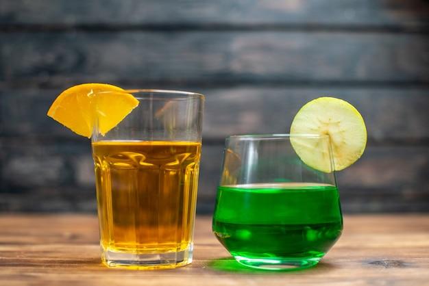 Front view fresh fruity juice orange and apple drinks inside glasses on brown wooden desk