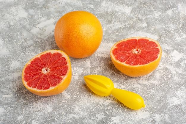 Вид спереди свежие грейпфрутовые кольца сочных и спелых цитрусов на белой поверхности