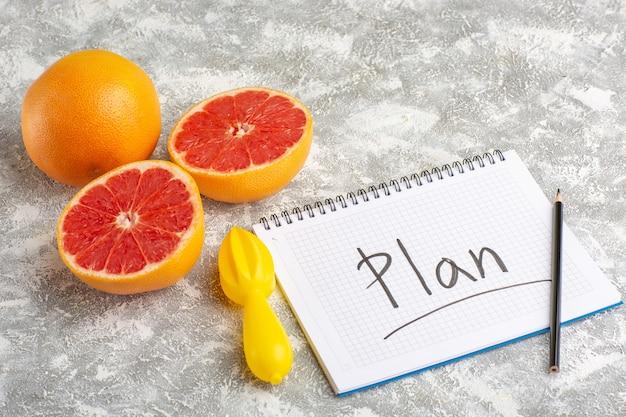 Вид спереди кольца свежего грейпфрута с блокнотом и карандашом на белой поверхности