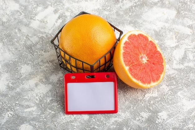 Вид спереди свежие грейпфруты, спелые и сочные цитрусы на белой поверхности