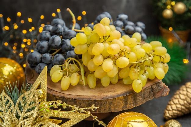 暗い背景のフルーツワインの色のクリスマスのクリスマスのおもちゃの周りの新鮮なブドウの正面図