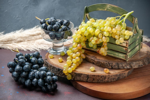 Front view fresh grapes green and black fruits on dark surface wine grape fruit ripe fresh tree plant