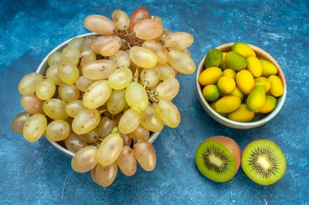 Вид спереди свежий виноград внутри тарелки на синем соке спелые цветные фрукты спелые фото