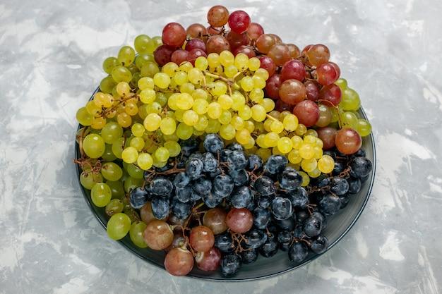 Vista frontale frutta succosa e pastosa dell'uva fresca all'interno del piatto sulla superficie bianca