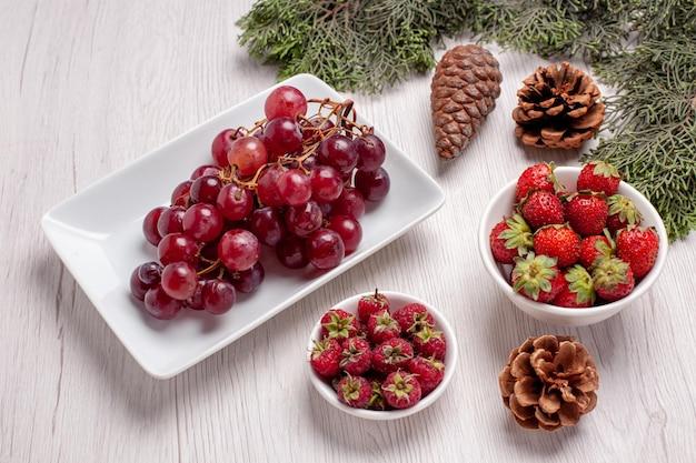 Vista frontale uva fresca con frutta su scrivania bianca frutta colore morbido succo