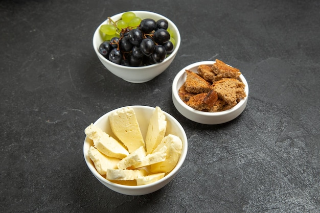 어두운 책상 식사 음식 접시 우유 과일에 흰색 치즈와 얇게 썬 검은 빵을 곁들인 신선한 포도