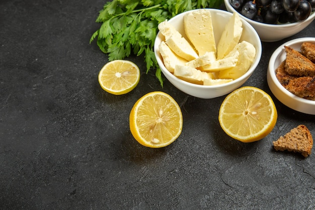 正面図新鮮なブドウと白いチーズグリーンと暗い背景のレモンスライス食事朝食料理ミルクフルーツ 無料写真