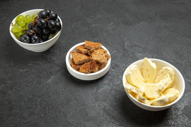 Vista frontale uva fresca con formaggio bianco e pane scuro affettato sullo sfondo scuro pasto cibo piatto frutta latte