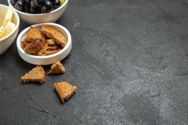 Vista frontale uva fresca con formaggio bianco e pane scuro a fette su fondo scuro pasto piatto cibo frutti di latte