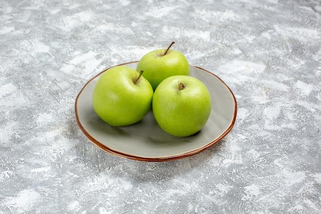 Вид спереди свежие зеленые яблоки внутри тарелки на белой поверхности свежие спелые спелые фрукты пищевой витамин