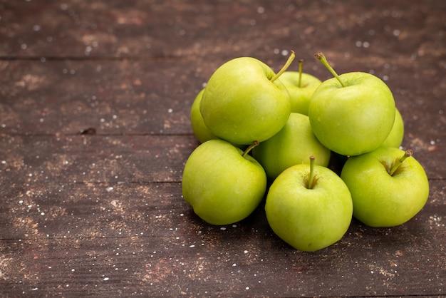 木製の机に分離された正面の新鮮な緑のリンゴ