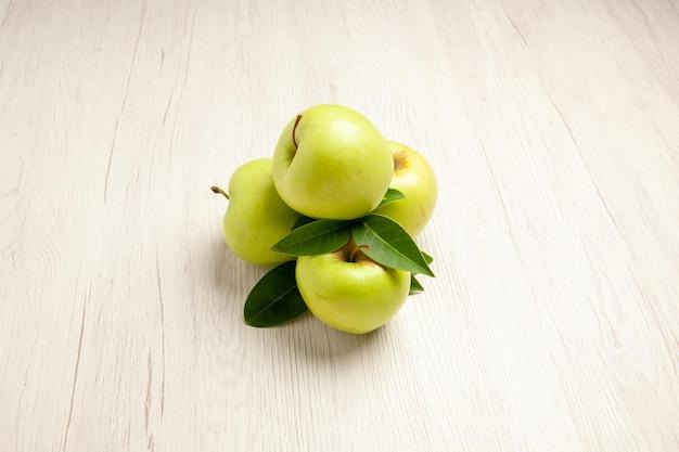Vista frontale mele verdi fresche frutti dolci e maturi su un albero bianco fresco di colore della pianta della scrivania