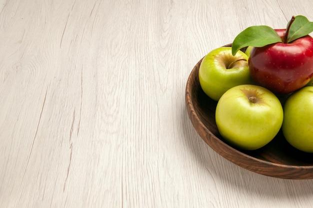 Vista frontale mele verdi fresche frutti maturi e morbidi sulla scrivania bianca albero colore frutta pianta fresca rossa