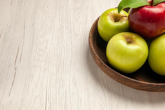 Vista frontale mele verdi fresche frutti maturi e morbidi sulla scrivania bianca frutti colorano pianta fresca rossa