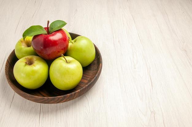 Vista frontale mele verdi fresche frutti maturi e morbidi sul pavimento bianco albero colore frutta pianta fresca rossa