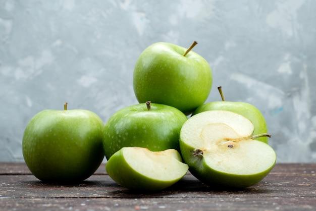 Вид спереди свежие зеленые яблоки нарезанные и целые на серый