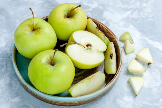Vista frontale mele verdi fresche affettate e frutti interi sulla superficie bianco-chiaro frutta fresca e morbida vitamina matura
