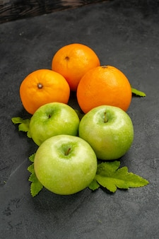Front view fresh green apples with oranges on a grey background ripe photo color tree fruit juice vitamine