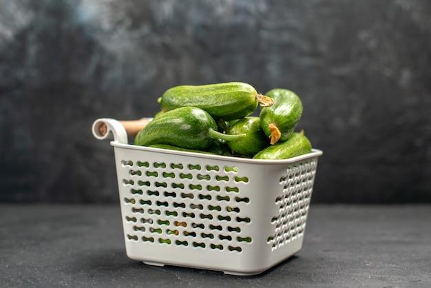 Vista frontale cetrioli verdi freschi all'interno del cestello su sfondo scuro foto insalata pasto cibo salute colore