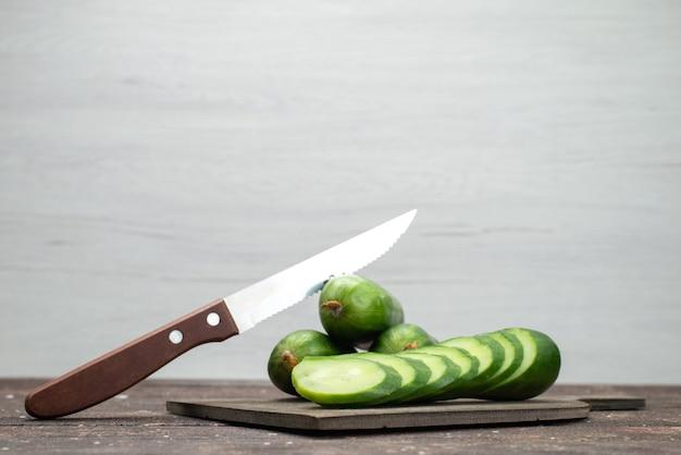 Вид спереди свежие зеленые огурцы целые и нарезанные на белый, овощная еда еды