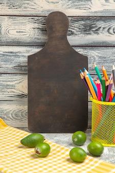 Feijoa verde fresco di vista frontale con le matite colorate su fondo grigio frutta tropicale esotica