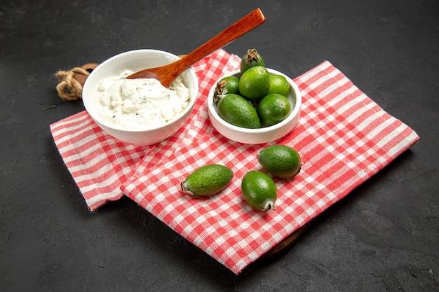 正面図新鮮な緑のフェイジョアとクリーム色の暗い表面の果物のエキゾチックな健康